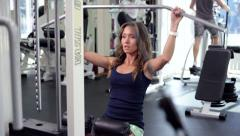 Stock Video Footage of Young Woman Uses Lat Machine (training apparatus)