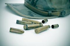 A camouflage cap and some bullets and bullet shells Stock Photos