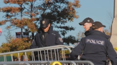 Police officers moving metal barriers, war memorial Stock Footage