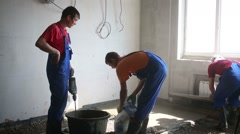 Three workers prepare mixture for pouring floor in room Stock Footage