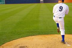 baseball pitcher throwing on the mound - stock photo