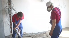 Two workers prepare mixture for floor in unfinished apartments Stock Footage