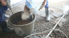 Two workers prepare mixture for pouring concrete floor Stock Footage