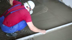 Worker in respirator makes overlay of concrete floor - stock footage