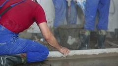 Worker makes screed of floor and two workers prepare mixture Stock Footage