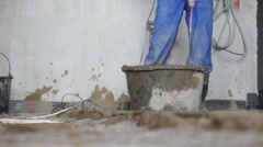 Legs and drill of worker preparing concrete mixture Stock Footage