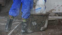 Legs of two workers preparing concrete mixture Stock Footage