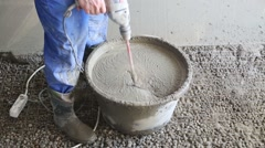 Legs and hands of worker in gumboots preparing concrete grout Stock Footage