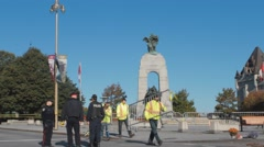 Police Officers by war memorial, Ottawa, moving metal barriers Stock Footage