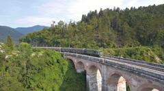 Aerial - Cargo train crosses the old stone railroad bridge Stock Footage