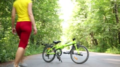 Young woman raises seat and steering wheel of bike and rides Stock Footage