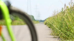 Back of woman riding bicycle on road next to transmission line - stock footage