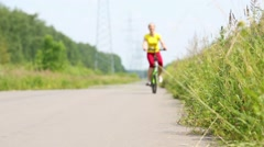 Slim young woman rides bicycle on road next to transmission line Stock Footage
