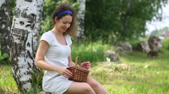 Young woman in white looks at basket and smiling outdoor Stock Footage