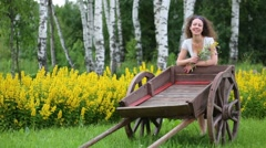Young woman stands next to old cart with wildflowers and goes Stock Footage
