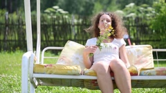 Beautiful woman in dress sits on swing with pillows and smiles - stock footage