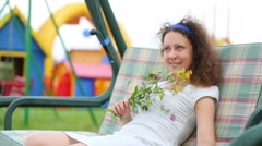 woman sits on swing and man sits down next to her and swings - stock footage