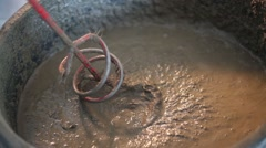 Rotating whisk of mixer immersed in concrete mix in bucket Stock Footage