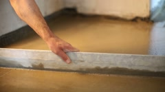 Hand of man making screed of concrete floor in room Stock Footage