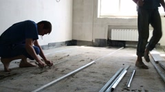 Two workers prepare underlayment for concrete floor Stock Footage