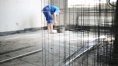 Light grey metal grid for pouring concrete floor and working man Stock Footage