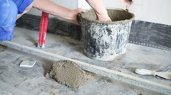 Hand of worker putting by trowel concrete solution from bucket Stock Footage