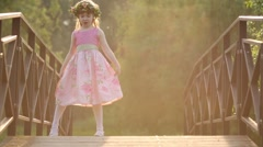 Little girl in pink dress and wreath dances on bridge in park Stock Footage