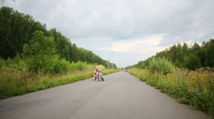 Boy rides bicycle and girl roller skate on road in summer Stock Footage