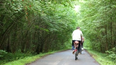 Back of two men riding bikes on track in summer park Stock Footage