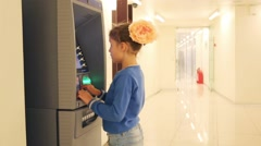 Girl stands near automatic teller machine in office building Stock Footage