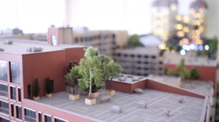 Talking boy looks at layout of buildings with trees on roof Stock Footage