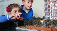 Talking boy and girl look at layout of buildings and touch water Stock Footage