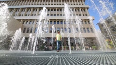 Boy in yellow t-shirt stands among many fountains at sunny day Stock Footage
