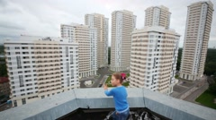 Girl in blue looks at new buildings on roof at cloudy summer day Stock Footage