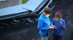 Top view of happy girl and boy standing with phone at roof Stock Footage