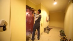 Back of man in overall removing plaster from door jamb - stock footage