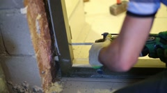 Hands of worker making hole using drill for install metal door Stock Footage