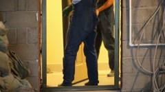 Legs of two men in overalls installing new door in apartment Stock Footage