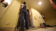 Two young workers work with door frame in new apartment Stock Footage