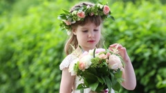 Little pretty girl in white dress and wreath touches bouquet Stock Footage