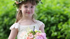 Little pretty girl in white dress and wreath holds bouquet Stock Footage