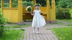 Little pretty girl in dress and wreath goes from carved arbor Stock Footage