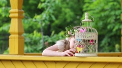 Little pretty girl in wreath plays with cage with butterflies Stock Footage