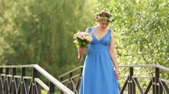 Beautiful happy woman in blue dress with bouquet spins in park Stock Footage