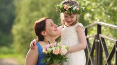 Mother with bouquet and little daughter in wreath talk and kiss Stock Footage