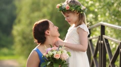 Pretty mother with bouquet and little daughter in wreath talk Stock Footage