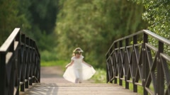 Little pretty girl in white dress and wreath runs on bridge Stock Footage