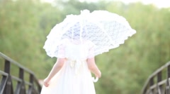 Back of little girl with lace umbrella going on bridge in park Stock Footage