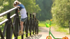 Little girl stands next to scooter on bridge and looks down Stock Footage