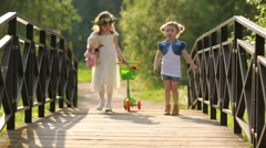 Two little girls go with scooter on bridge at summer day Stock Footage